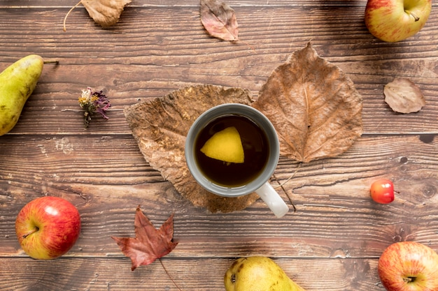Cup with lemon tea among autumn fruits