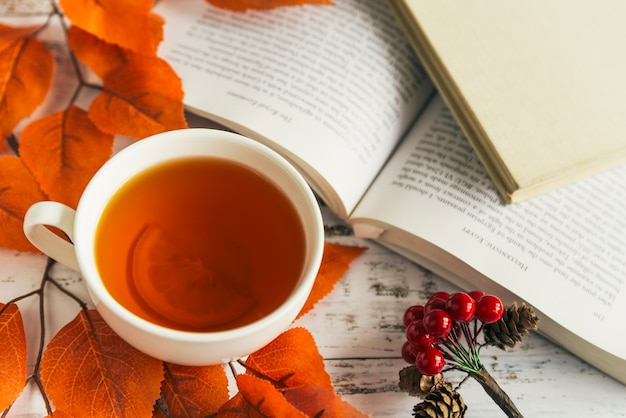 Cup with lemon tea and book among autumn leaves