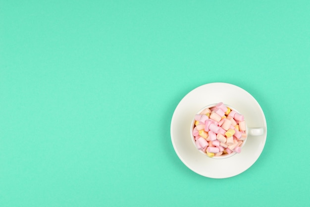 Cup with marshmallow on a green background. copy space.