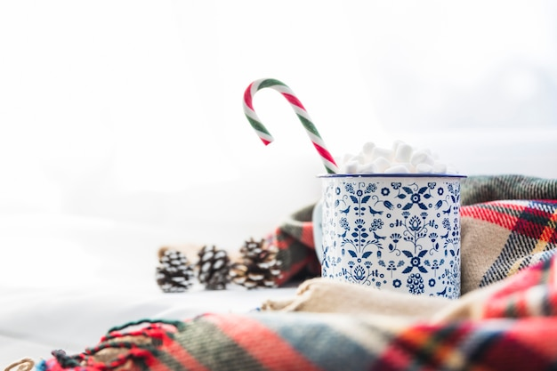 Cup with marshmallow and lollipop near scarf and snags