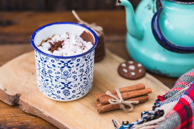 Cup with marshmallow near biscuits, cinnamon and kettle