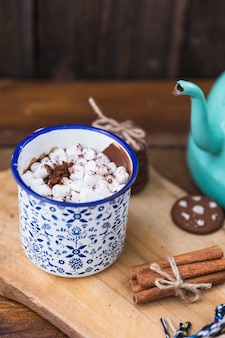 Cup with marshmallow near biscuits andcinnamon