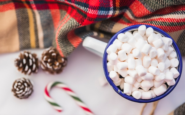 Cup with marshmallow near candy cane and snags