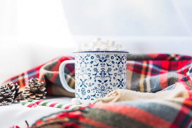 Cup with marshmallow near scarf and fir snags
