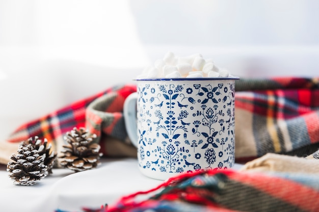 Cup with marshmallow near scarf