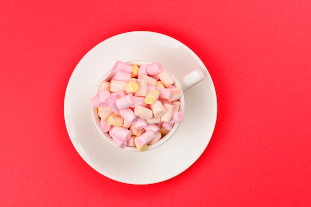 Cup with marshmallow on a red background. copy space.