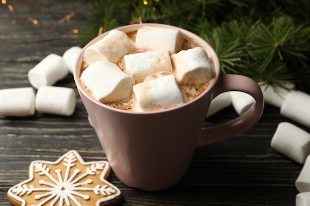 Cup with marshmallow on wooden table with christmas accessories