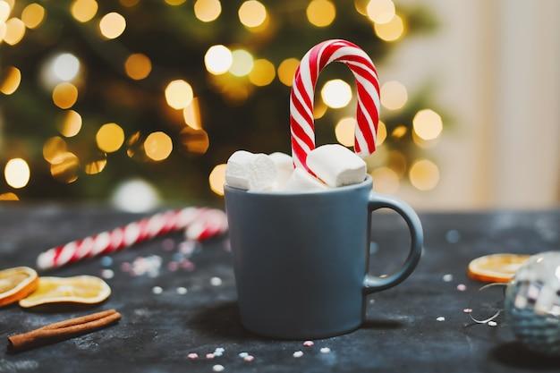 クリスマスツリーの背景でマシュマロキャンディケインタンジェリンとカップ新年の静物