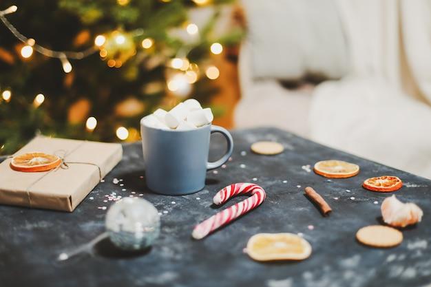 Чашка с зефиром, леденцы, мандарины на фоне елки, новогодний натюрморт