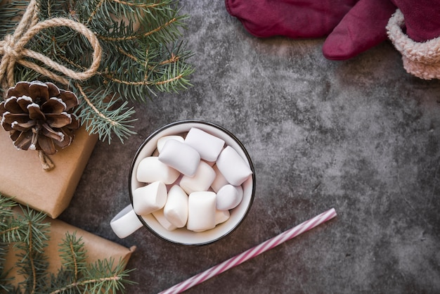 Cup with marshmallows near plastic tube, fir twigs and present boxes
