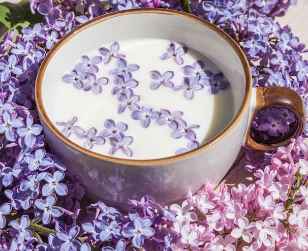 牛乳と小さな紫色のライラックの花とカップ