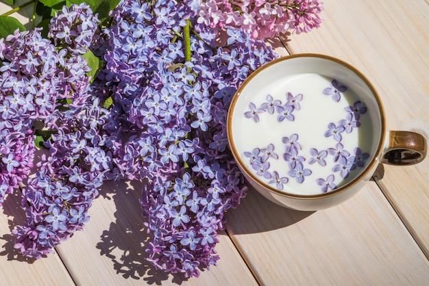ミルクと小さな紫色のライラックの花のカップ