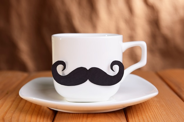Cup with mustache on table on brown surface
