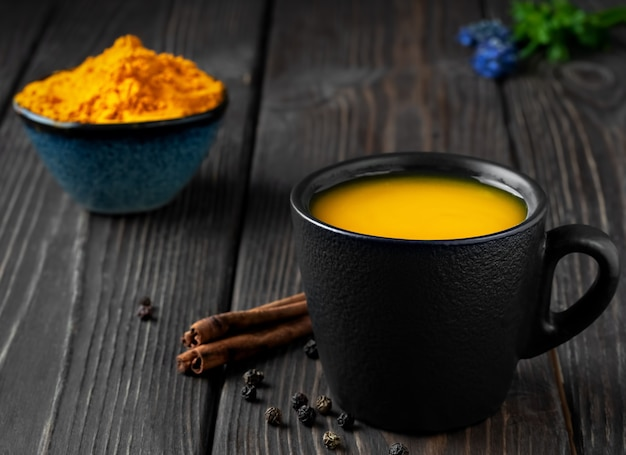 Cup with natural healthy herbal tea made from turmeric, honey and spices