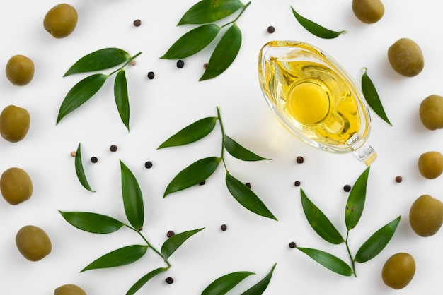 Cup with olive oil surrounded by leaves and olives