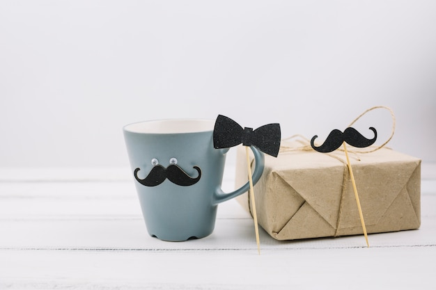 Cup with ornamental mustache near box and bow tie on wand