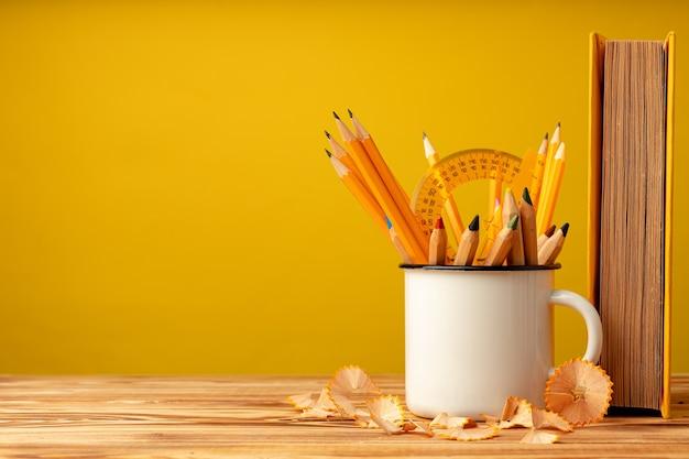 Чашка с карандашами и стружкой карандашей на деревянном столе на желтом фоне