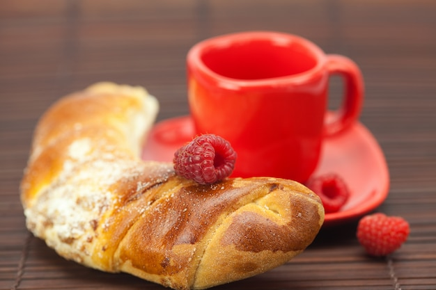 Cup with a plate , raspberry and roll on a bamboo mat