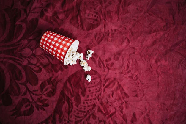 Cup with popcorn on velvet cloth