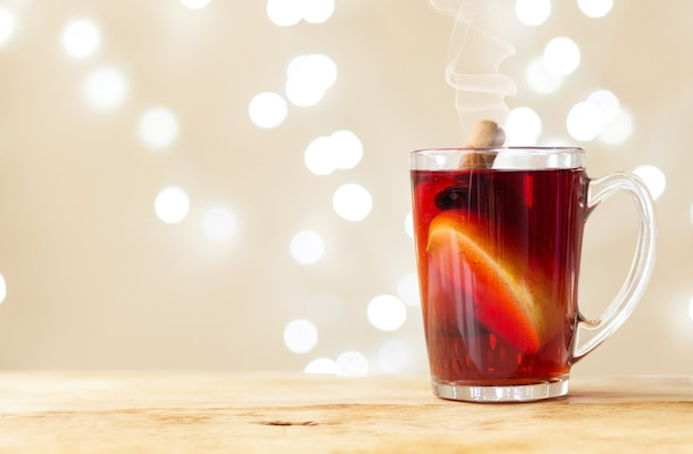 A cup with red mulled wine stands on a wooden tray on a light color background with bokeh