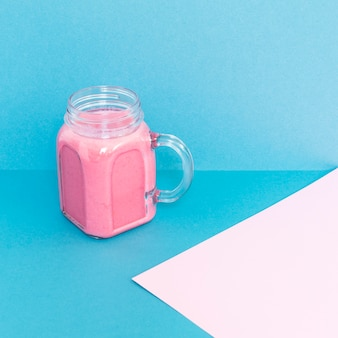 Cup with smoothie on table