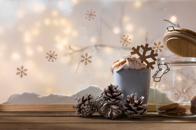 Cup with snags and can on wood table near bank of snow, plant twig, snowflakes and fairy lights