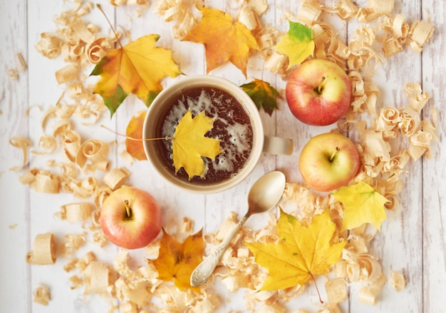 Cup with tea on an autumn background with apples, leaves and flowers.
