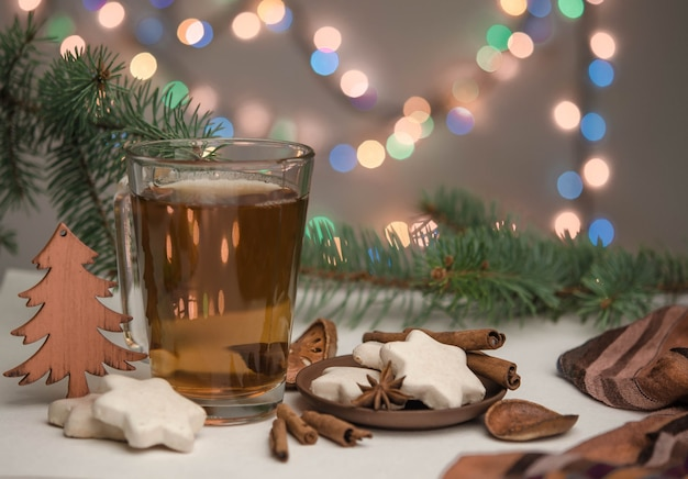 A cup with tea, gingerbread and christmas tree branches