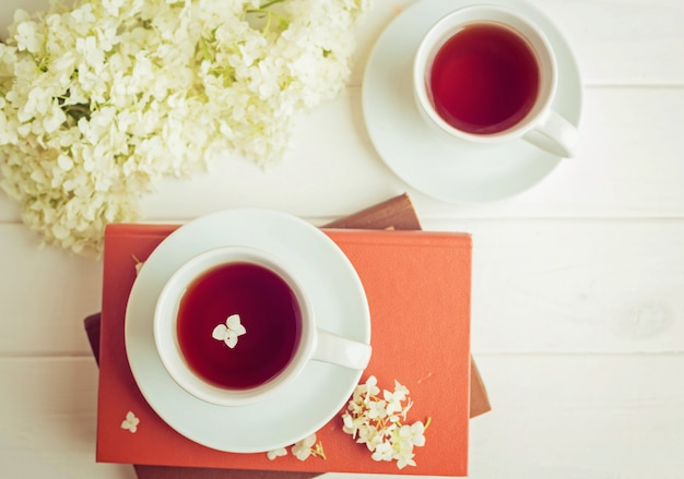 A cup with tea stands on books on a white background. heart shaped flowers. morning romantic breakfast.