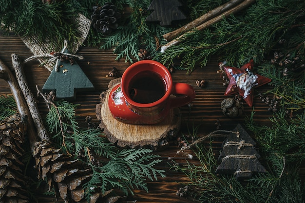 Cup with tea with branches of a christmas tree and cones on an old wood