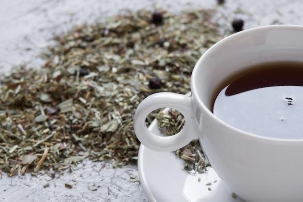Чашка с чаем с лимоном и сухими зеленью на деревянном фоне