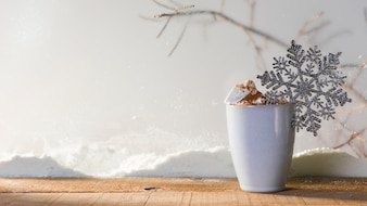 Cup with toy snowflake on wood table near bank of snow