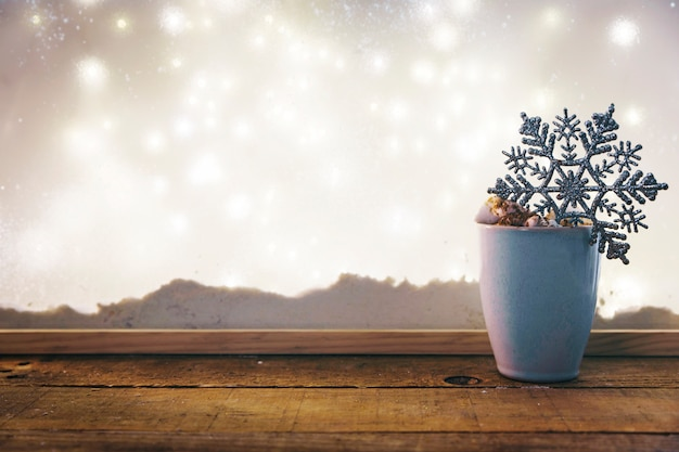 Cup with toy snowflake on wood table near bank of snow and fairy lights