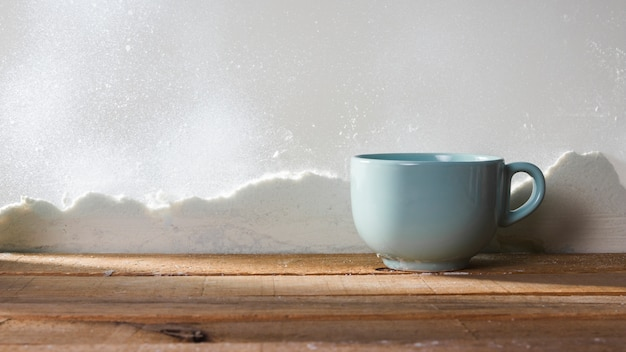 Cup on wood table near bank of snow and snowflakes