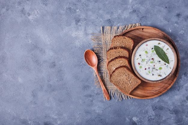 Una tazza di zuppa di yogurt servita con fette di pane.