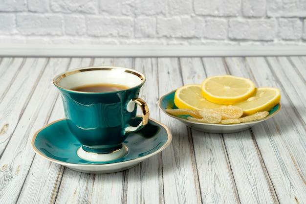 グリーンカップの熱いお茶とソーサーレモンと木製のテーブルに砂糖漬けの生cup