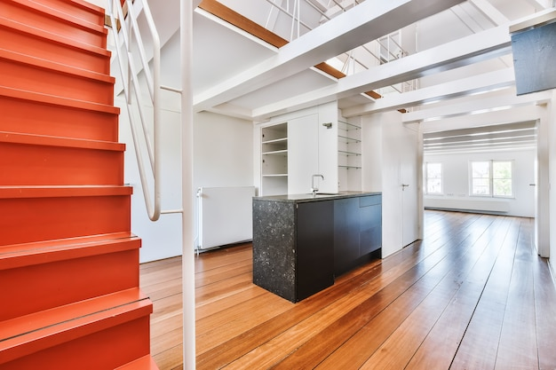 Cupboards with sink located in empty kitchen near orange stairway to mezzanine in spacious contemporary flat