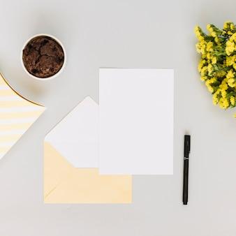 紙の葉の近くのカップケーキと花