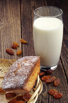 Кекс и стакан молока на старинном деревянном столе