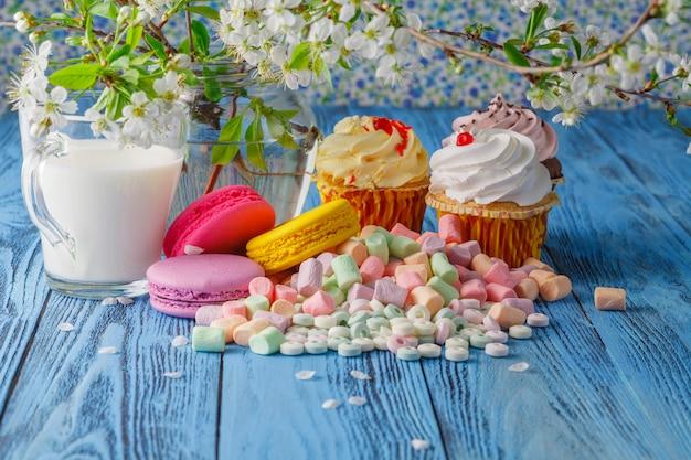 Кекс и миндальное печенье, зефир на столе