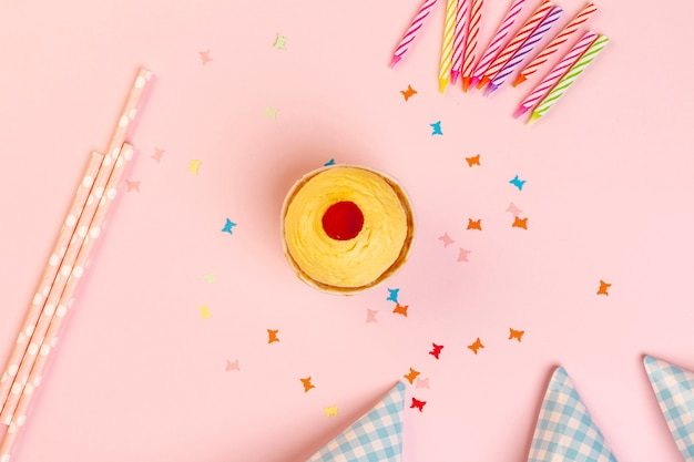 Cupcake and birthday decorations on a pink background