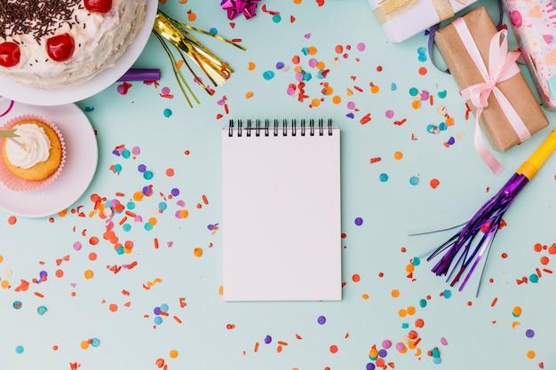 カップケーキケーキ;ギフト用の箱。ホーンブロワー空白のスパイラルメモ帳と青い背景に紙吹雪