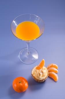 ジュースのグラスとカップケーキクリームケーキ