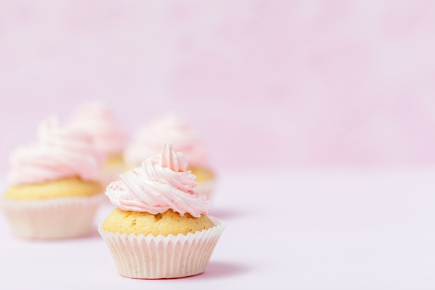Cupcake decorated with pink buttercream on pastel pink background. sweet beautiful cake.