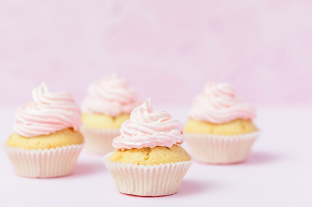 Cupcake decorated with pink buttercream on pastel pink background.