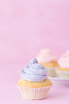 Cupcake decorated with pink and violet buttercream on pastel pink background
