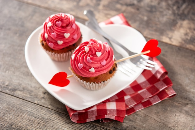 나무 테이블에 발렌타인 데이를위한 설탕 하트와 큐피드 화살로 장식 된 컵 케이크