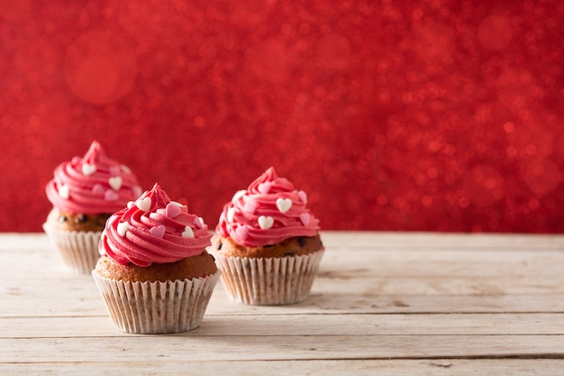 Cupcake decorated with sugar hearts and a cupid arrow for valentine's day on wooden table