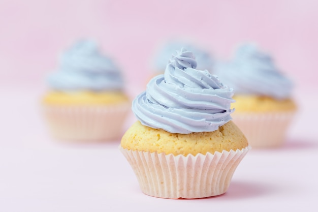 Cupcake decorated with violet buttercream on pastel pink background.