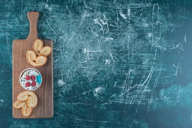 Un cupcake e biscotti traballanti impacchettati su una tavola su sfondo blu. foto di alta qualità